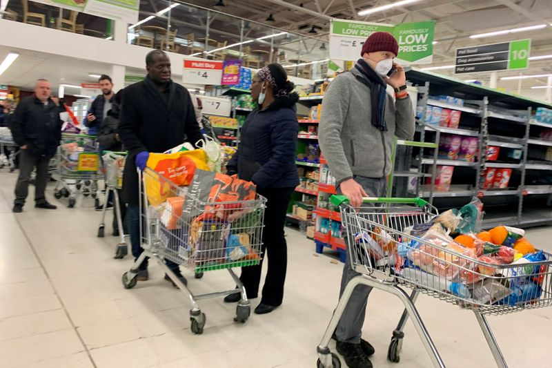 FILE PHOTO: Shoppers queue at a supermarket in London