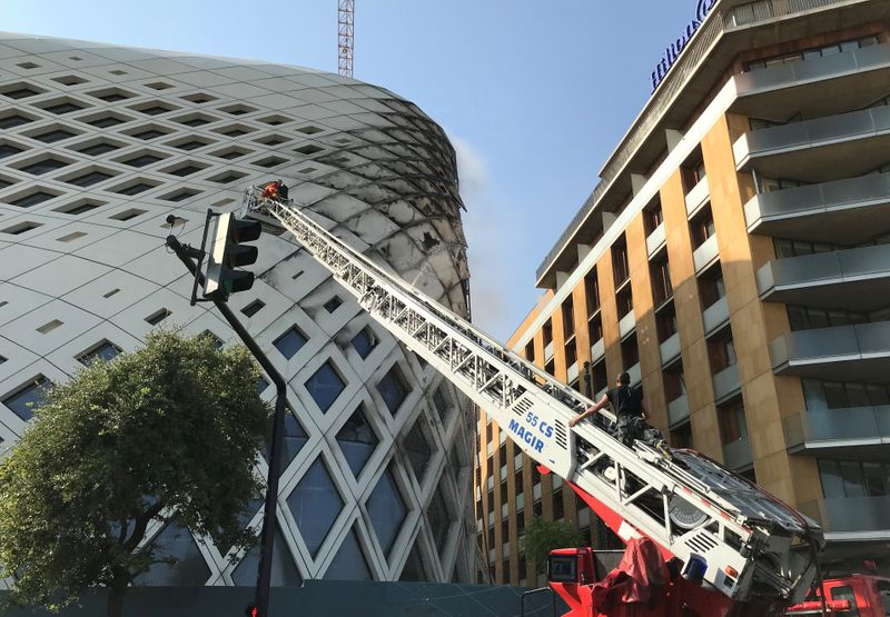 Civil defence members participate in efforts to put out a fire that broke out in a building in Central Beirut