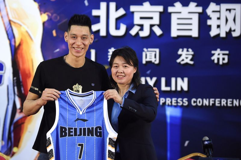 FILE PHOTO: Former NBA star Jeremy Lin poses with his Beijing Ducks jersey at a news conference in Beijing