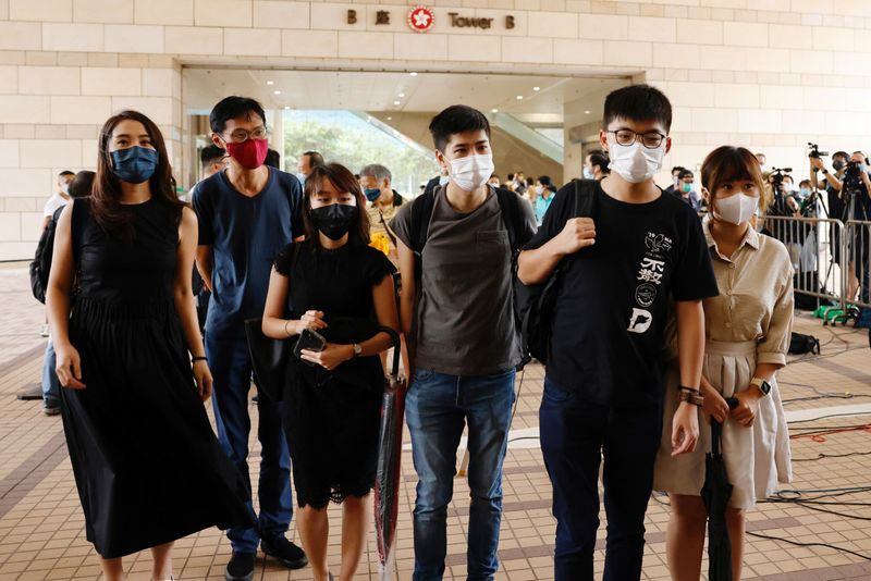 Pro-democracy activists, including Joshua Wong, Eddie Chu and Lester Shum arrive at the West Kowloon Courts before entering a courtroom to face charges related to illegal assembly during Tiananmen vigil, in Hong Kong