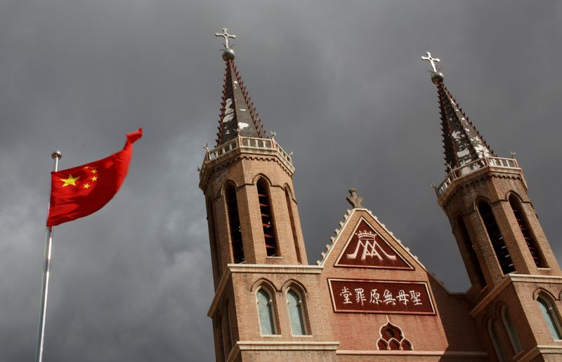 FILE PHOTO: The Chinese national flag flies in front of a Catholic church in the village of Huangtugang