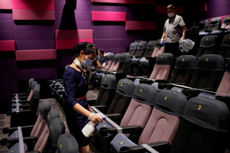 A staff member wearing a face mask disinfects seats in a cinema as it reopens following the coronavirus disease (COVID-19) outbreak, in Shanghai