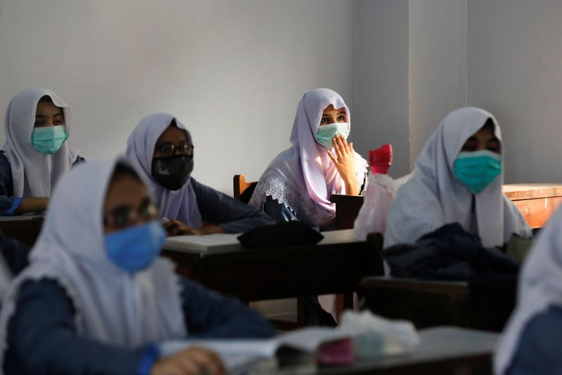 Students wear protective masks while maintaining safe distance as they attend a class as schools reopen amid the coronavirus disease (COVID-19) pandemic, in Karachi,