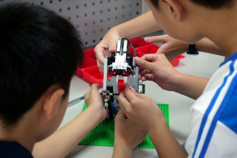 FILE PHOTO: Elementary school students build a motion sensor controlled disinfectant dispenser from Lego parts during a workshop, following a novel coronavirus outbreak, in the southern Taiwanese city of Kaohsiung