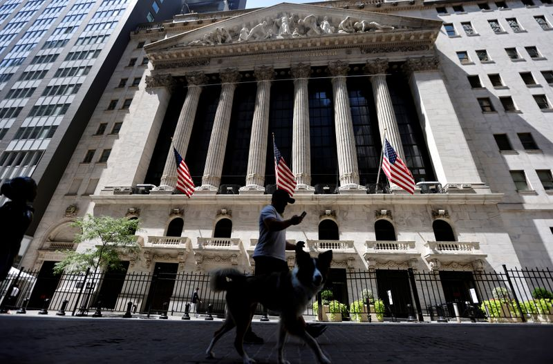 FILE PHOTO: A man walks a dog in the shade past the New York Stock Exchange (NYSE) during hot weather in New York