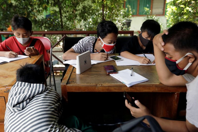 Dimas Anwar Saputra studies with other students at a local district office in Jakarta