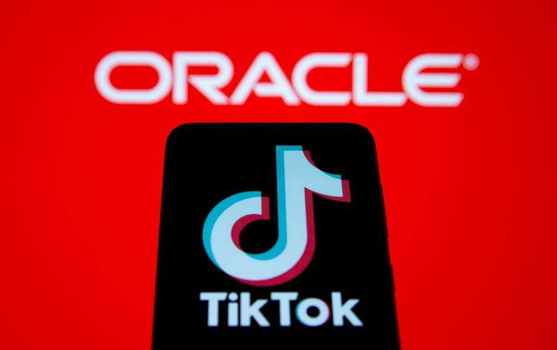 Smartphone with Tik Tok logo is seen in front of displayed Oracle logo in this illustration