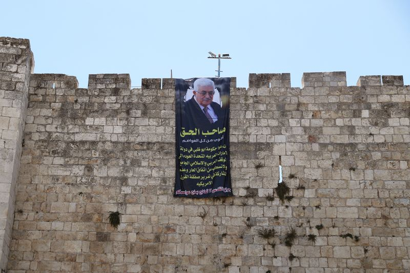 FILE PHOTO: Palestinian President Mahmoud Abbas is depicted on a banner hung on the surrounding walls of Jerusalem's Old City