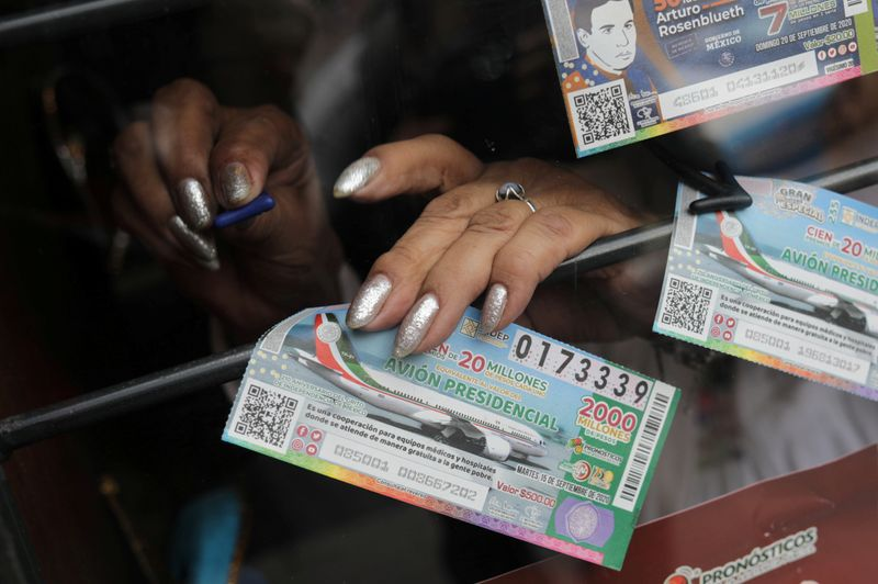 A Mexican lottery salesperson arranges lottery tickets for a Mexico presidential plane for sale at a raffle ticket booth, in Mexico City