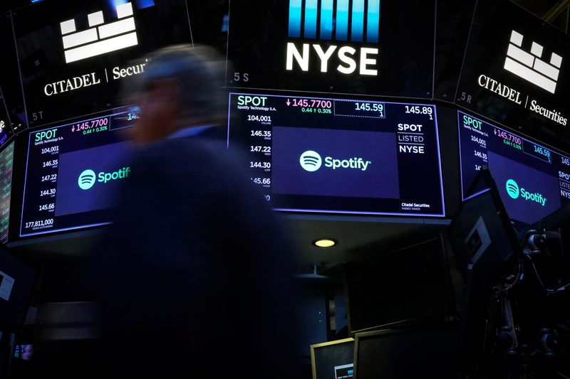 A trader passes by screens showing Spotify on the floor at the NYSE in New York