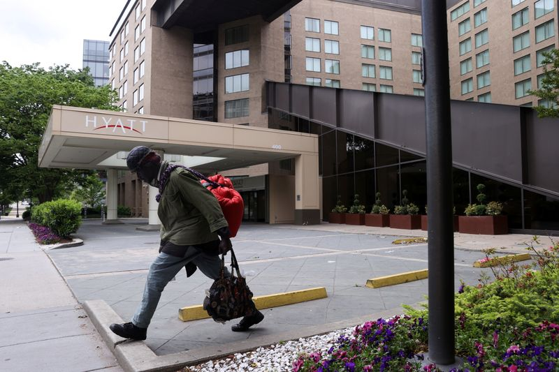 A member of the homeless community walks past a Hyatt hotel that is completely closed to guests during the coronavirus disease (COVID-19) outbreak, in Washington
