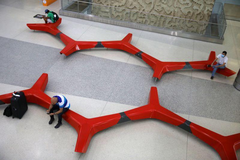 Passengers practice 'social distancing' at a main Miami International Airport terminal