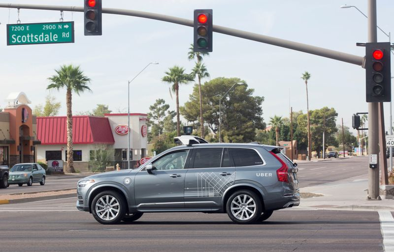 FILE PHOTO: A self driving Volvo vehicle, purchased by Uber, moves through an intersection in Scottsdale, Arizona,