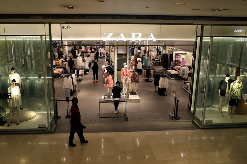 FILE PHOTO: Staff wearing protective mask waits for customers at the entrance of a Zara store, amid the coronavirus disease (COVID-19) outbreak in Kuala Lumpur