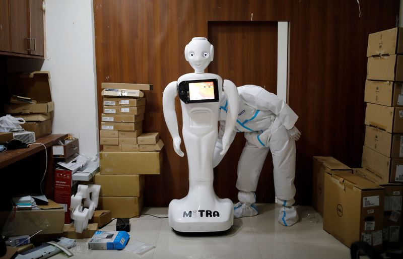 A medical worker puts robot named 'Mitra' , which is used by the patients suffering from the coronavirus disease (COVID-19) to communicate with their relatives, on charge at a Hospital in Noida