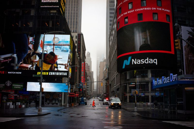 FILE PHOTO: A man walks near Nasdaq MarketSite in an empty Times Square