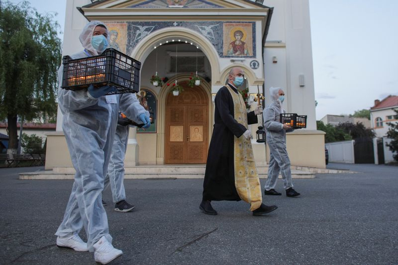 Orthodox priest Bogdan Teleanu, wearing a face mask, and volunteers carrying crates of lit candles while dressed in protective suits, head to the surrounding streets to bring holy light to people celebrating Orthodox Easter