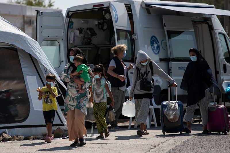 A family from the destroyed Moria camp for refugees and migrants arrives at a new temporary camp, on the island of Lesbos