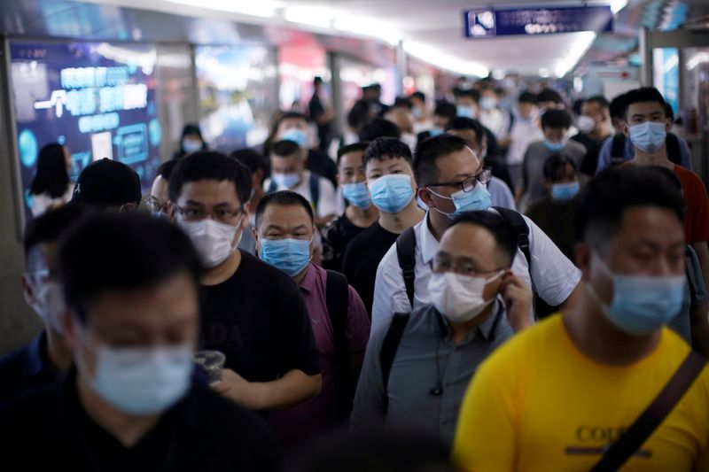 People wearing face masks arrive at Yiwu Railway Station