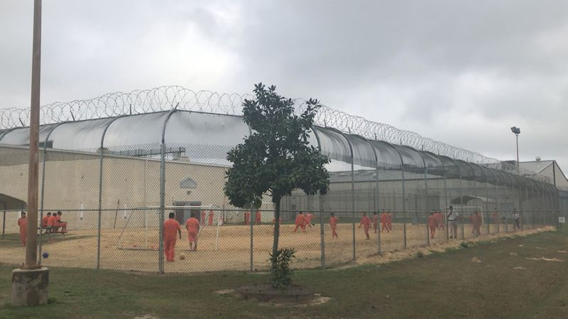 Detained immigrants play soccer behind a barbed wire fence at the Irwin County Detention Center in Ocilla
