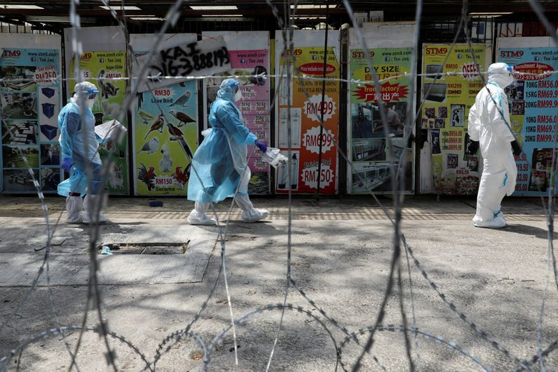 FILE PHOTO: Medical workers wearing protective suits pass by barbed wire at the red zone under enhanced lockdown, amid the coronavirus disease (COVID-19) outbreak, in Petaling Jaya