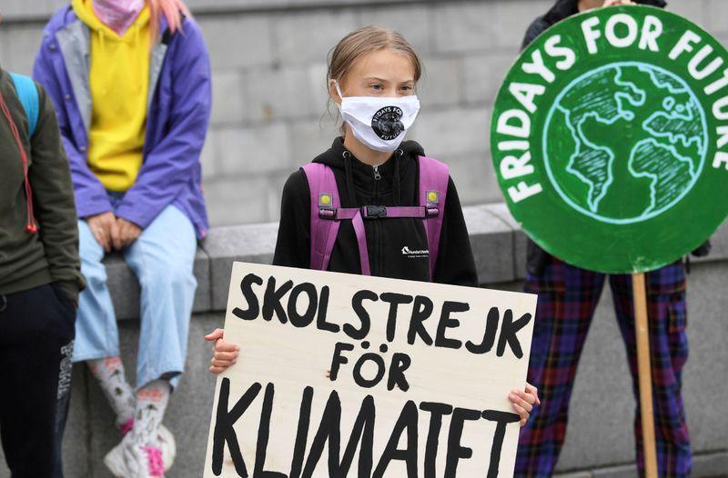 FILE PHOTO: Swedish climate activist Greta Thunberg holds a poster reading