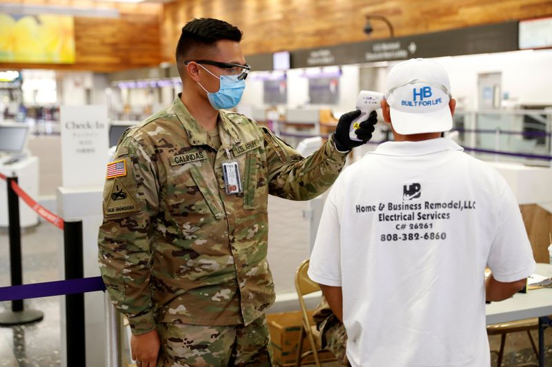 A Hawaii National Guardsman checks the temperature of a traveler at the Daniel K. Inouye International Airport during the spread of the coronavirus disease (COVID-19) in Honolulu