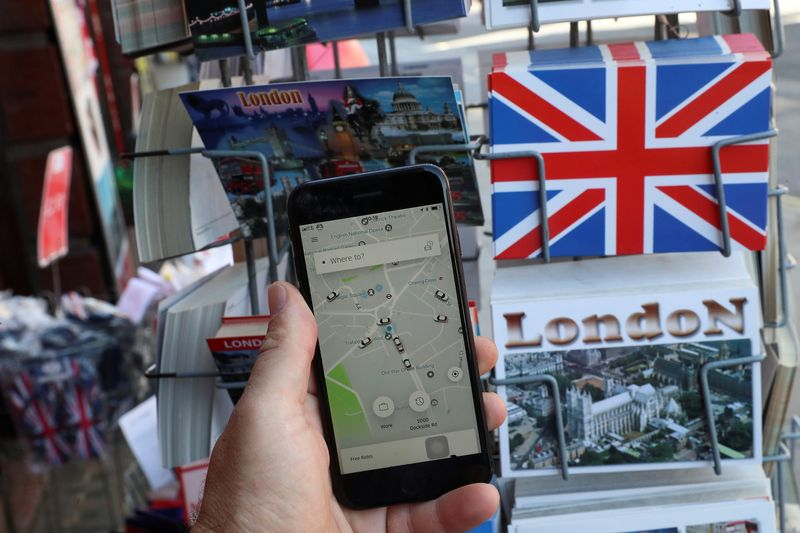 FILE PHOTO: A photo illustration shows the Uber app and London themed postcards in London