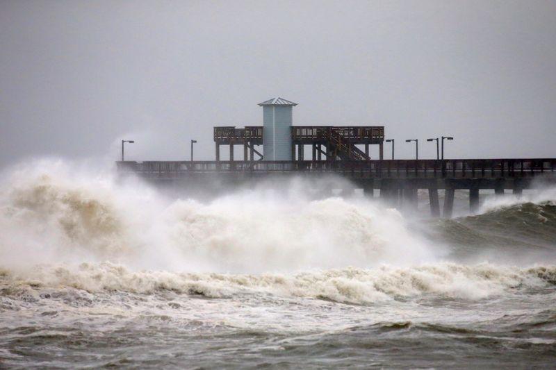 FILE PHOTO: Waves crash along a pier as Hurricane Sally approaches in Gulf Shores