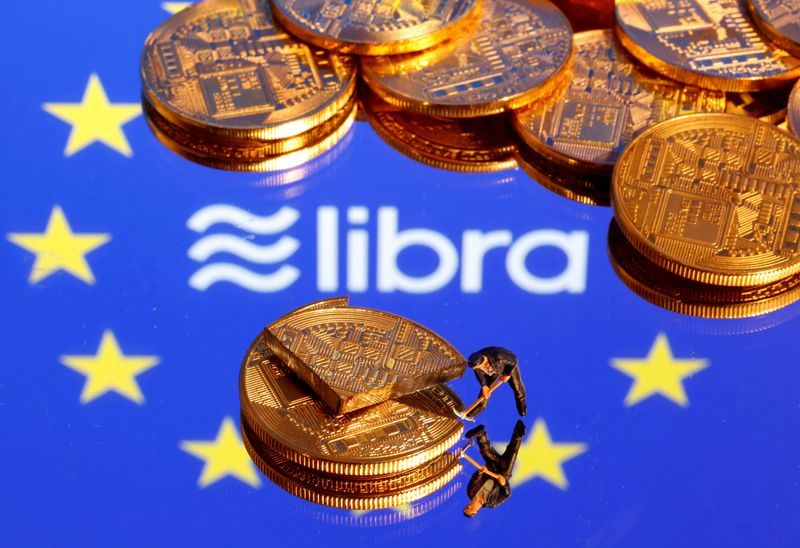 FILE PHOTO: A small toy figure is seen on representations of the virtual currency on a displayed European Union flag and the Facebook Libra logo in this illustration picture