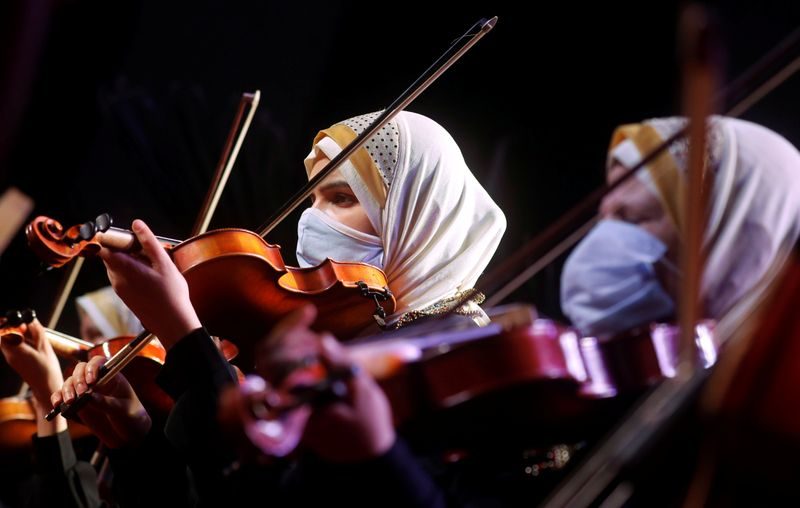 Members of Al-Nour Wal Amal (Light and Hope) chamber orchestra of blind women wearing protective masks play during their first concert at the Manasterly Palace in Cairo