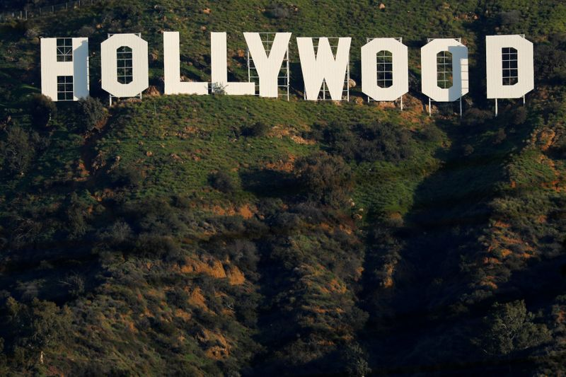 The iconic Hollywood sign is shown on a hillside above a neighborhood in Los Angeles