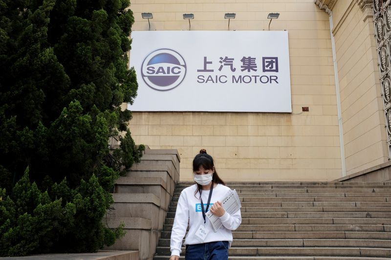 Woman wearing a face mask following the coronavirus disease (COVID-19) outbreak walks by a SAIC Motor logo at a sales event in Shanghai