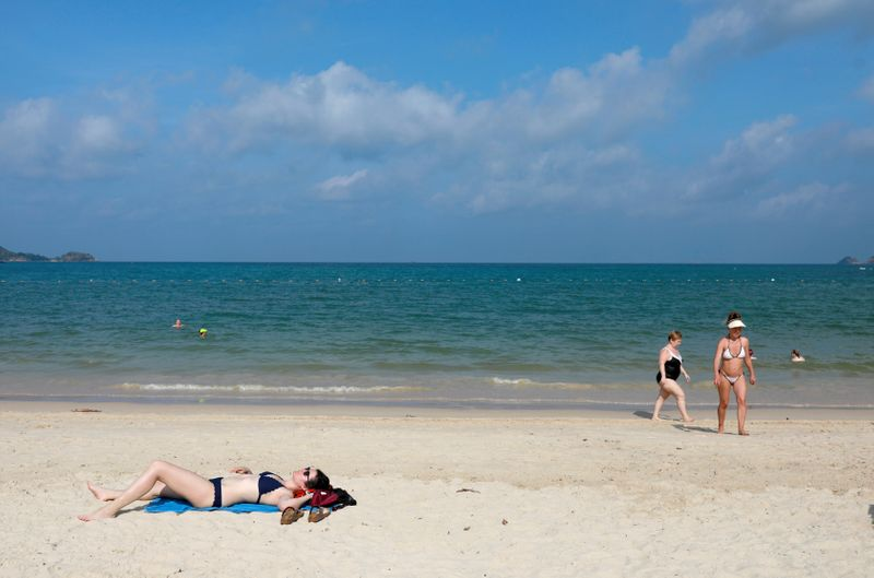 FILE PHOTO: FILE PHOTO: A few Western tourists are seen on a beach which is usually full of Chinese tourists, amid fear of coronavirus in Phuket