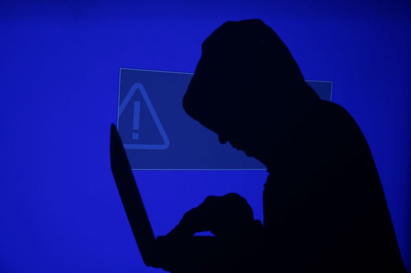 Hooded man holds laptop computer as blue screen with an exclamation mark is projected on him in this illustration picture