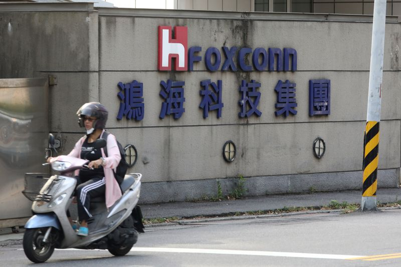 A person riding a scooter wears a mask amid the outbreak of the coronavirus disease (COVID-19), while passing a Foxconn office building in Taipei