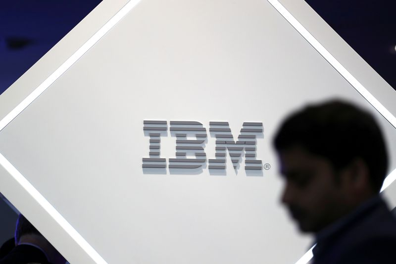 FILE PHOTO: Man stands near an IBM logo at the Mobile World Congress in Barcelona