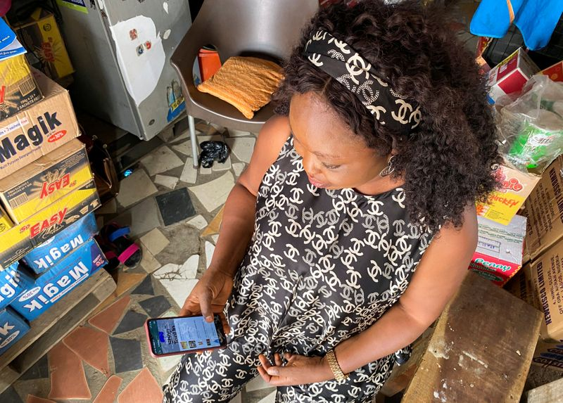 Kiosk store owner, Funmilayo Akinola, uses Trade Depot company's app inside her store in Lagos