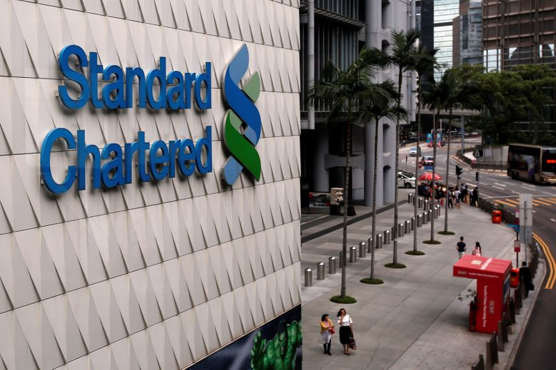 People walk outside the main branch of Standard Chartered in Hong Kong
