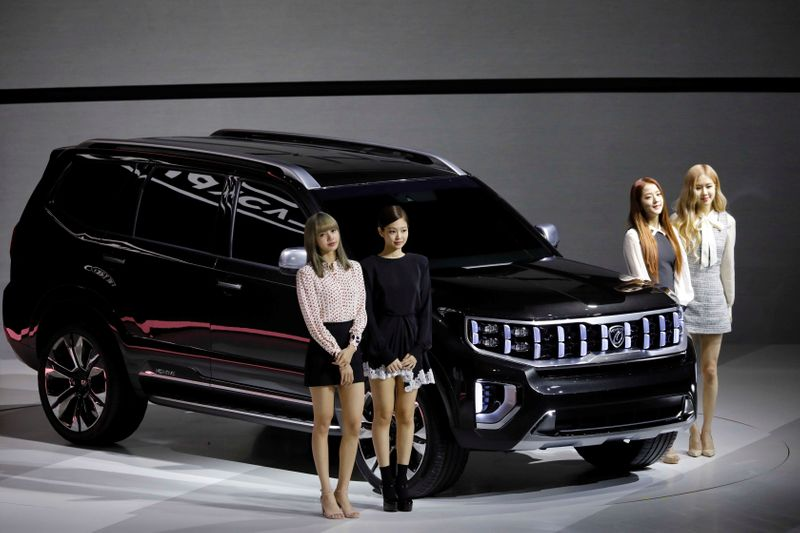 Members of K-pop idol group Black Pink pose for photographs with Kia Motors' Mohave during the 2019 Seoul Motor Show in Goyang