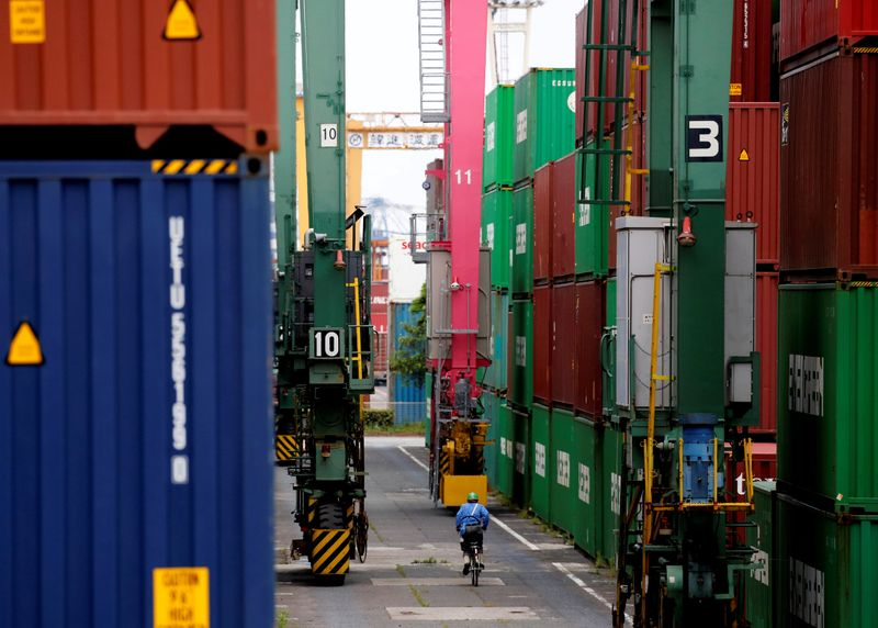 FILE PHOTO: A man on a bicycle rides past containers at an industrial port in Tokyo