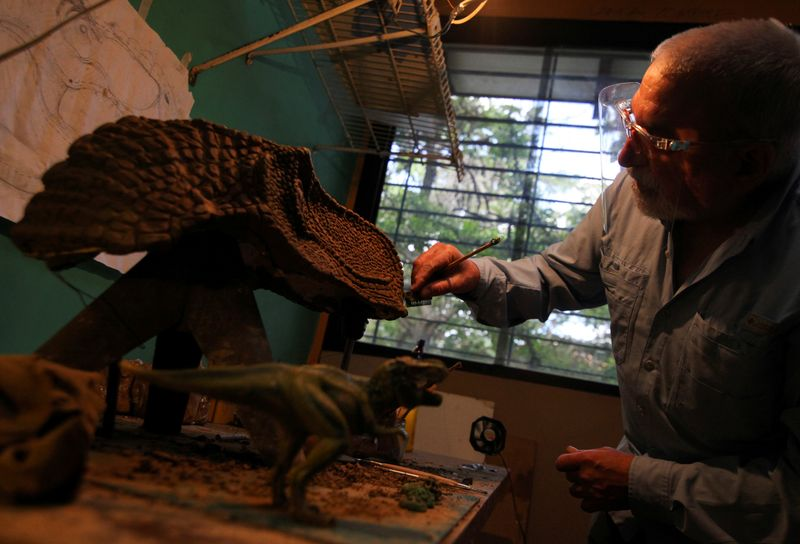 Alonso Toro, a professional musician who worked in television and advertising, makes a face mask imprinted with the image of a dinosaur as a toy for children during the coronavirus disease (COVID-19) pandemic, in Caracas