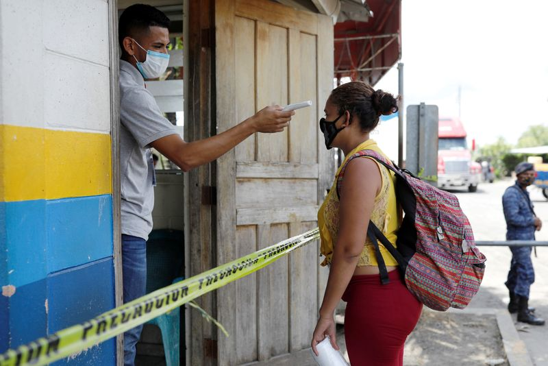 FILE PHOTO: A man checks the temperature of a migrant from Honduras who was trying to reach the U.S., at the Corinto border between Guatemala and Honduras, in Puerto Barrios