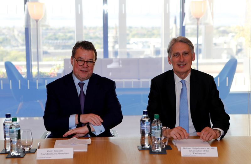 FILE PHOTO: Keith Skeoch CEO of Standard Life Aberdeen and Britain's Chancellor of the Exchequer Philip Hammond pose for a photograph in Edinburgh