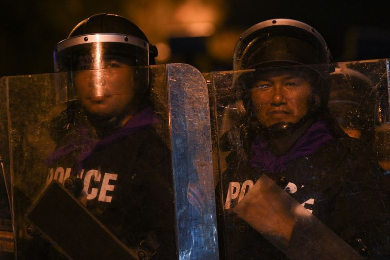Police officers with riot shields take position during a gathering of pro-democracy protesters who demand the government to resign and to release detained leaders in Bangkok