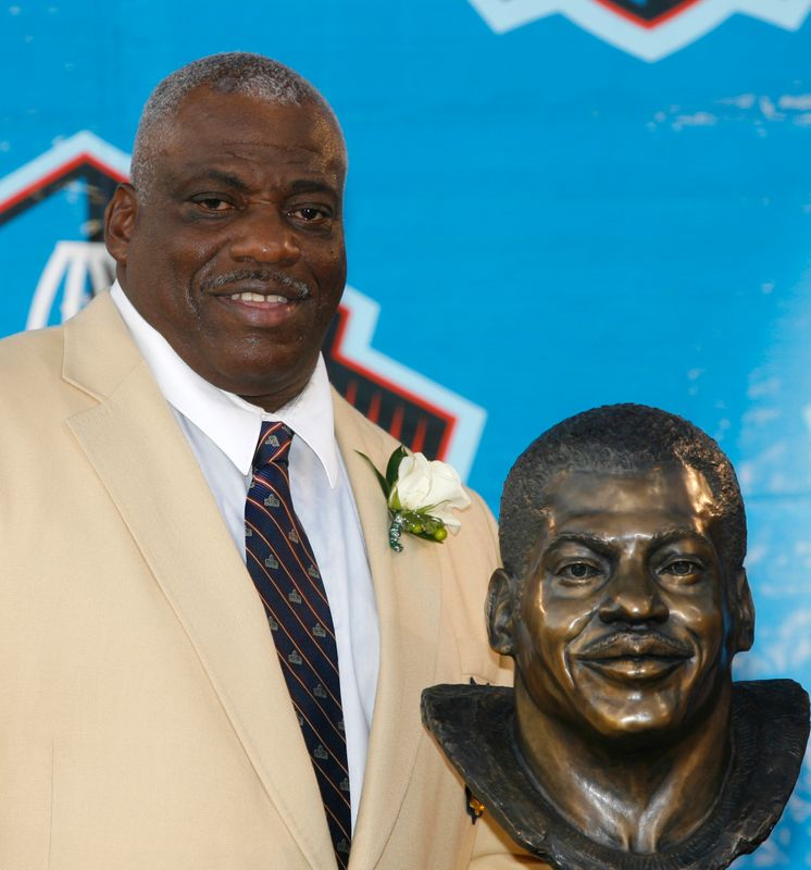 FILE PHOTO: Former NFL player Fred Dean poses with his bust after being inducted into the Pro Football Hall of Fame in Canton