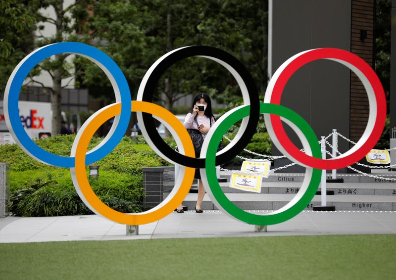 A woman wearing a protective mask amid the coronavirus disease (COVID-19) outbreak, takes a picture of the Olympic rings in front of the National Stadium in Tokyo
