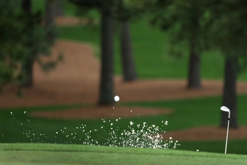 FILE PHOTO: Marc Leishman of Australia hits from a sand trap on the seventh hole during third round play of the 2018 Masters golf tournament in Augusta