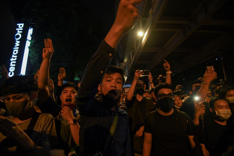 People show the three-finger salute during a gathering of pro-democracy protesters who demand the government to resign and to release detained leaders in Bangkok