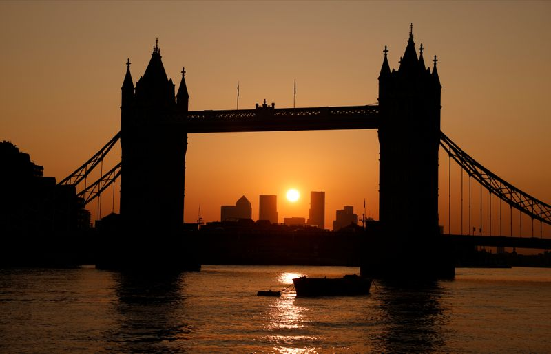 Tower Bridge with the Canary Wharf financial district in the background are seen at sunrise in London